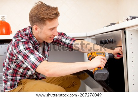 young worker installs a new electric cooker - stock photo