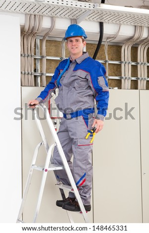 Young Worker Man With Hard Hat standing on ladder - stock photo