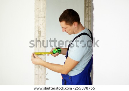 Young worker measuring the wall - stock photo