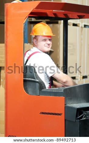 young worker men in uniform at warehouse with forklift stacker facilities - stock photo