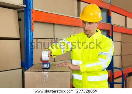 Young Worker Packing Cardboard Box With Tape Gun Dispenser In Warehouse - stock photo