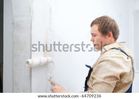 young worker painting wall with roller - stock photo