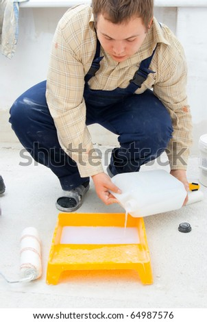 young worker pouring paint from a large bucket - stock photo