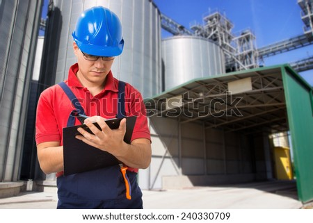 Young worker taking notes in front of silos company