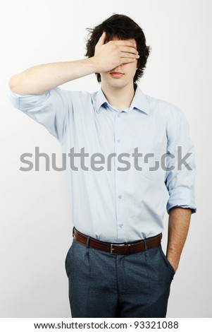 Young worker with his hand on his eyes - stock photo