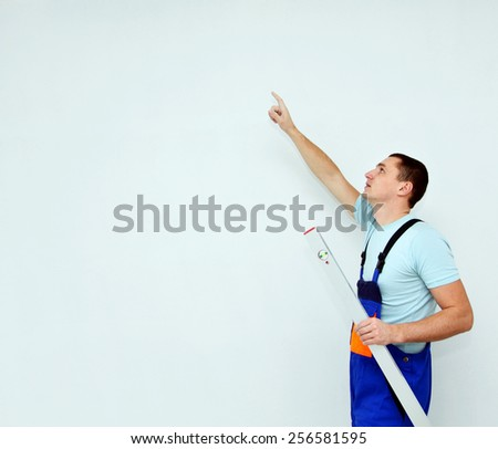 Young worker with level pointing - stock photo
