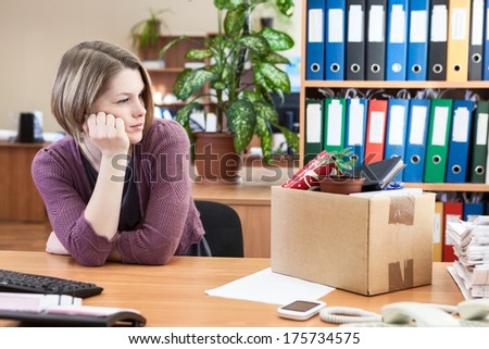 Young worker with regret looking at box with personal belongings on table - stock photo