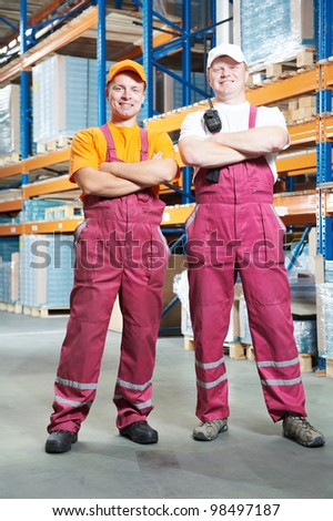 young workers men in uniform in front of warehouse rack arrangement stillages