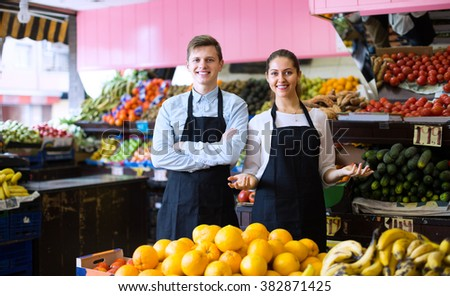 Young workers selling fresh fruits and eco vegetables on market