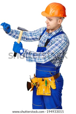 Young working man wearing protective clothes,gloves and helmet with hammer driving a nail in wall isolated on white background