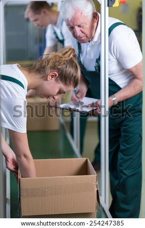 Young working woman checking the box in warehouse - stock photo