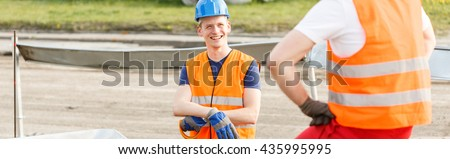 Young workman smiling to a friend on the construction site - stock photo