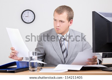 young worried accountant doing paperwork in office - stock photo
