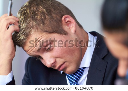 Young worried and stressed businessman scratch his head - stock photo