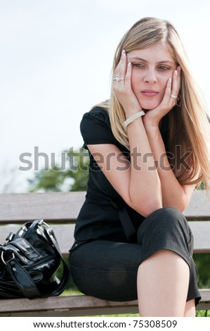 Young worried beautiful woman siting on bench - head in hands