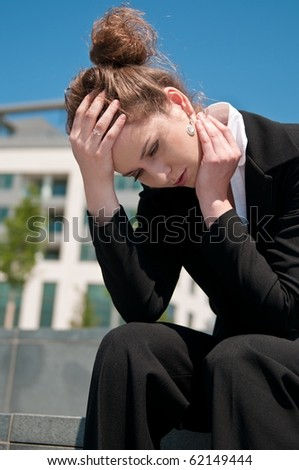 Young worried business woman siting outdoors - head in hand - stock photo