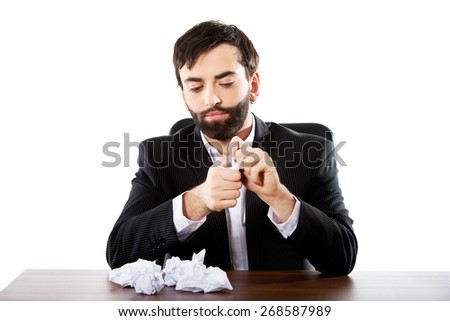 Young worried businessman crushing sheets. - stock photo
