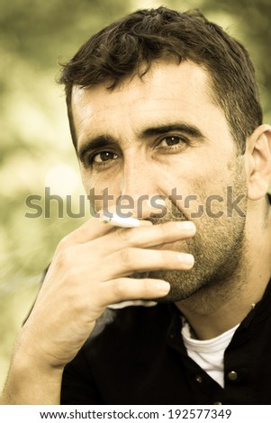 Young worried man smoking a cigarette and thinking about the problem - stock photo