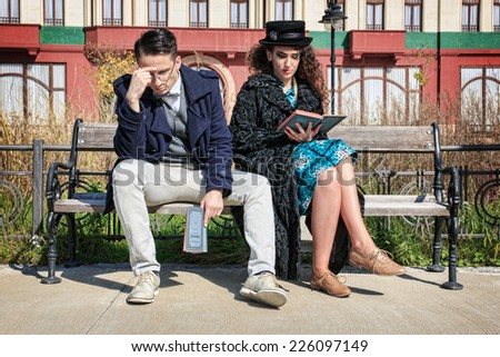 Young worried retro couple in quarrel sitting on bench reading book - stock photo