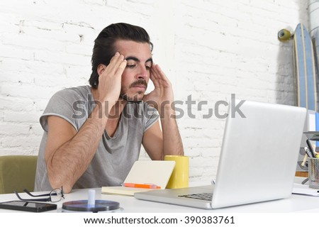 young worried student or businessman at computer suffering stress and headache looking overworked preparing exam or deadline over business project sitting at modern home office - stock photo