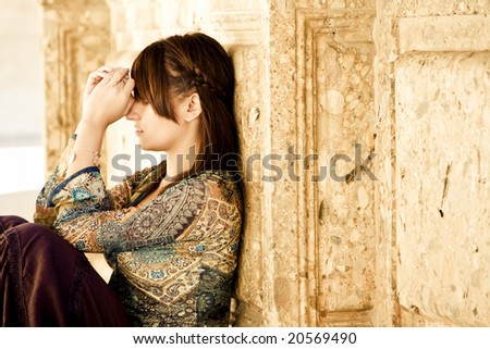 Young worried woman against old stone wall - stock photo