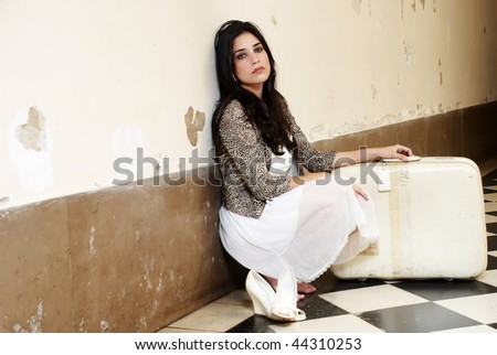 Young worried woman against old stone wall with an old suitcase - stock photo