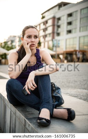 Young worried woman holding mobile phone received bad message - stock photo