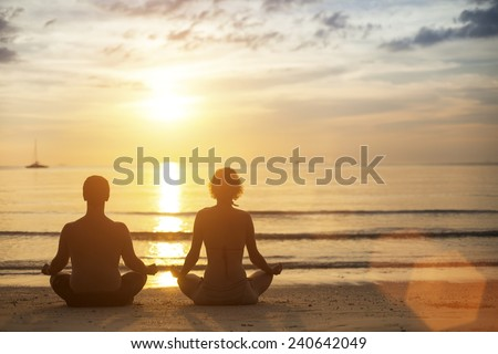 Young yoga couple meditating on the coast during the amazing sunset. - stock photo