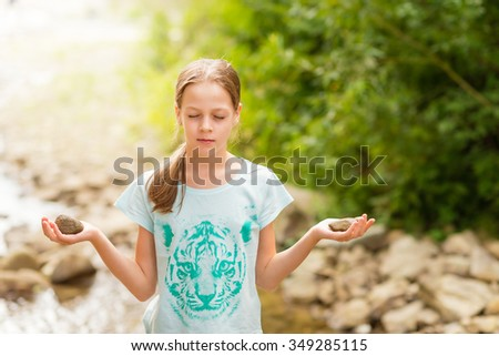 Young Yoga Girl meditating at sunrise in mountain stream. Female model meditating in harmony with stones in hands. Healthy wellness lifestyle image concept. Hand painted t-shirt with tiger motive