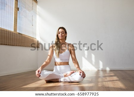 Young Yoga Woman Meditating Peacefully In A White Yoga Studio On Wooden  Floor Wearing White Sports