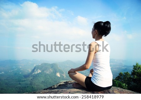 young yoga woman mountain peak - stock photo