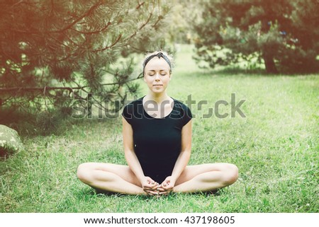 Young yoga woman practitioners yoga on nature. - stock photo