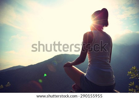 young yoga woman sit meditation on sunrise mountain peak rock - stock photo