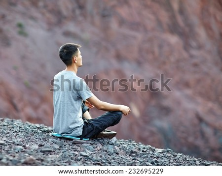 Young young man relaxing in yoga position on rocky cliff  - stock photo