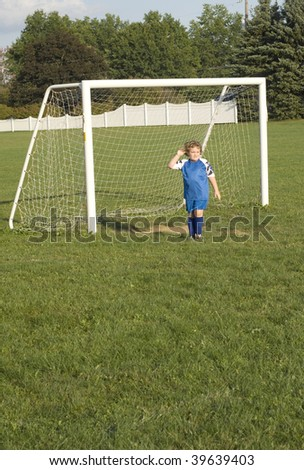 Young youth boy goalie standing in front of goal