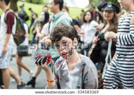 Young zombie boy holding blood in his hand at Sydney Zombie Walk, AU, 31st October, 2015. Annual event where thousands of people get involved to raise awareness for Australia's Brain Foundation. - stock photo