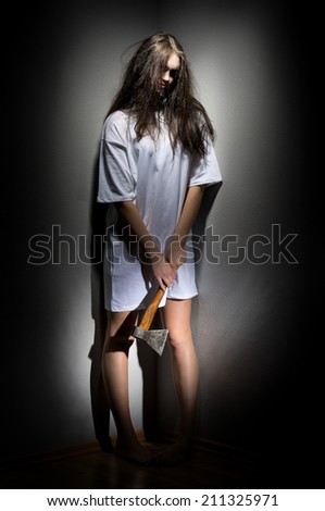 Young zombie girl with axe - stock photo