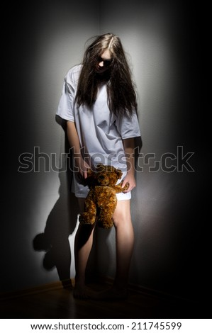 Young zombie girl with teddy bear - stock photo