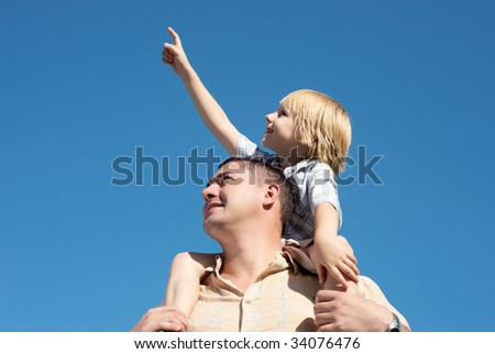 younger brother on shoulders at senior brother against the sky - stock photo