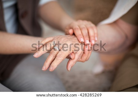 Younger hands holding an older hand - stock photo