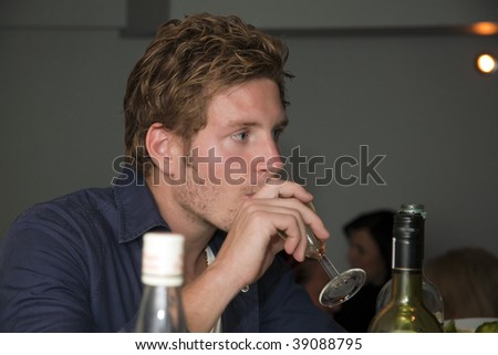 Youngster at the bar, drinking wine