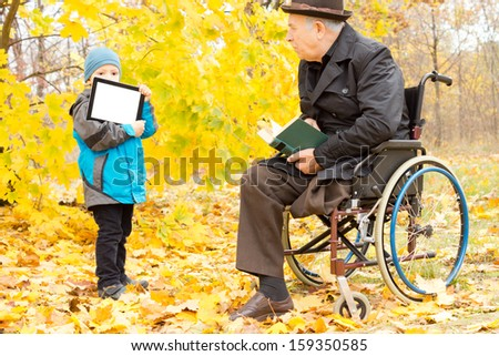 Youngster showing a disabled man a tablet-pc screen as the elderly gentleman sits in his wheelchair in a colourful yellow autumn park enjoying reading his book - stock photo