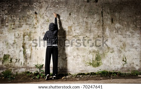 Youngster with spray paint and an empty wall for graffiti - stock photo