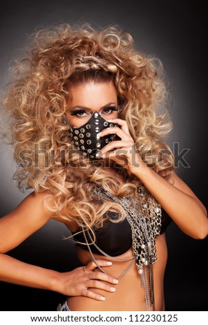 youns sexy sado masochist woman putting on her mask - stock photo
