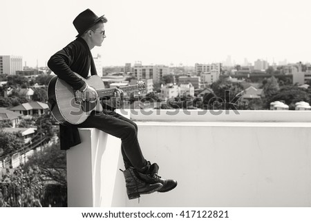 Youong caucasian man in black clothes and hat playing on acustic guitar - stock photo
