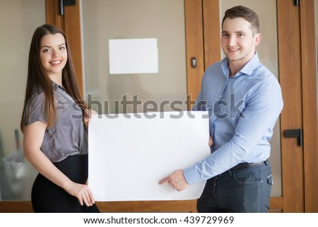 Your advertisement in good hands. Group of handsome young business people holding big blank with copy space - stock photo