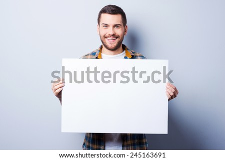 Your advertisement in good hands. Handsome young man holding copy space while standing against grey background - stock photo