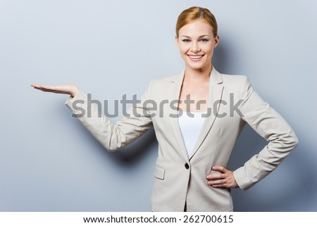 Your advertisement in her hand. Confident young businesswoman holding copy space and holding hand on hip while standing against grey background - stock photo