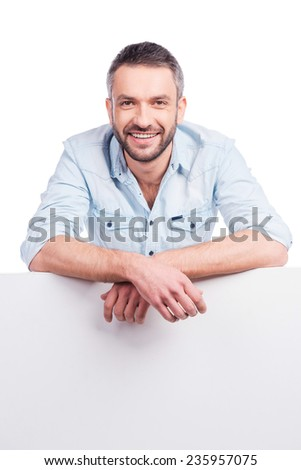 Your advertising below. Handsome young man in casual wear leaning at copy space and smiling while standing against white background - stock photo