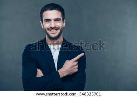 Your advertising here. Cheerful young man pointing at copy spaceand smiling while standing against grey background - stock photo